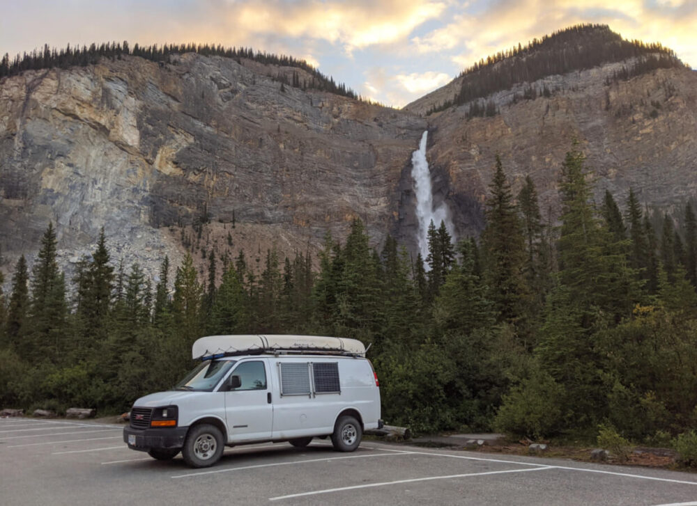White van with canoe on top (and solar panels on side) parked in empty parking lot in front of large waterfall