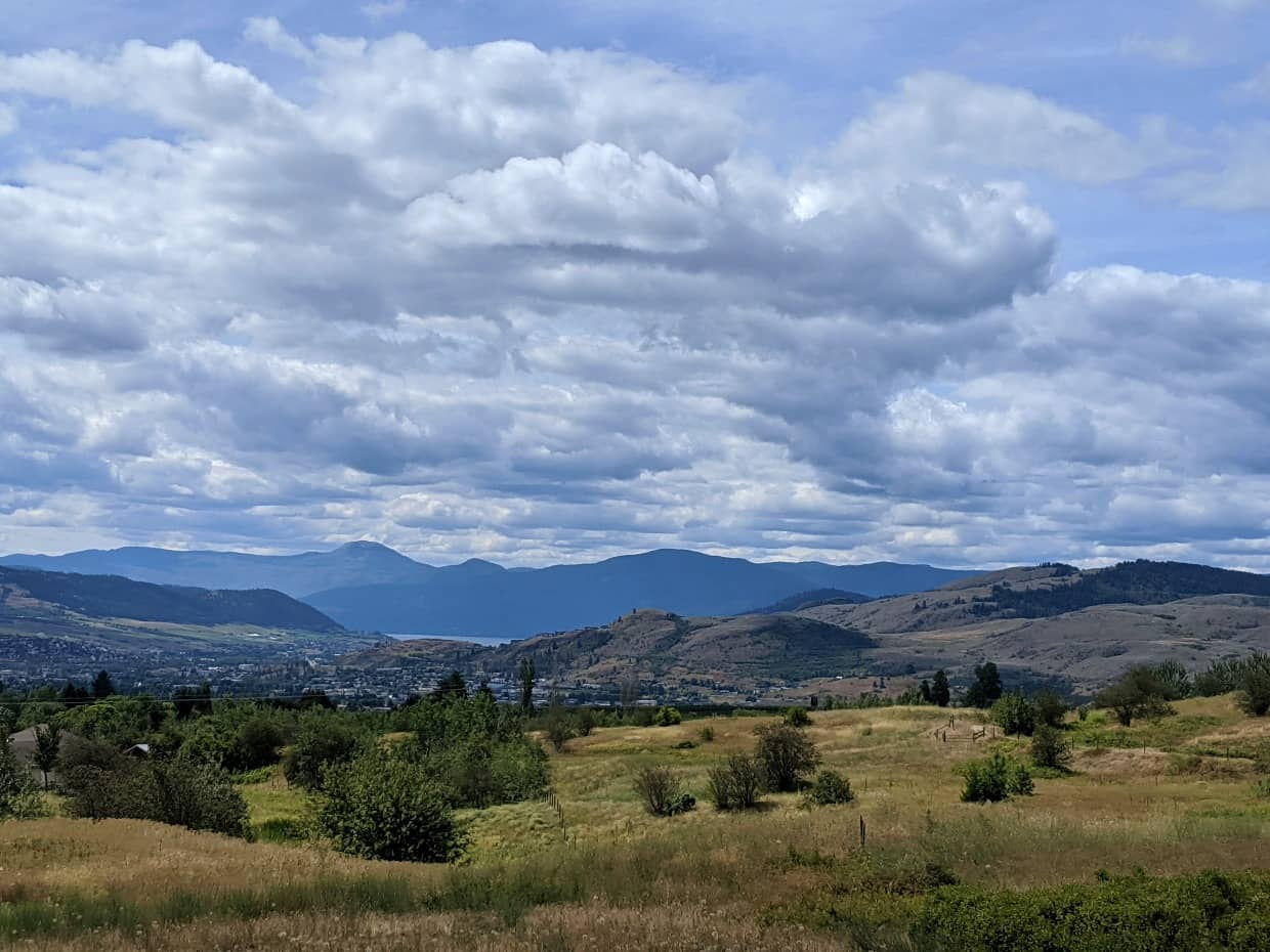 Elevated view looking down towards Vernon with rolling grasslands, mountains and lakeshore