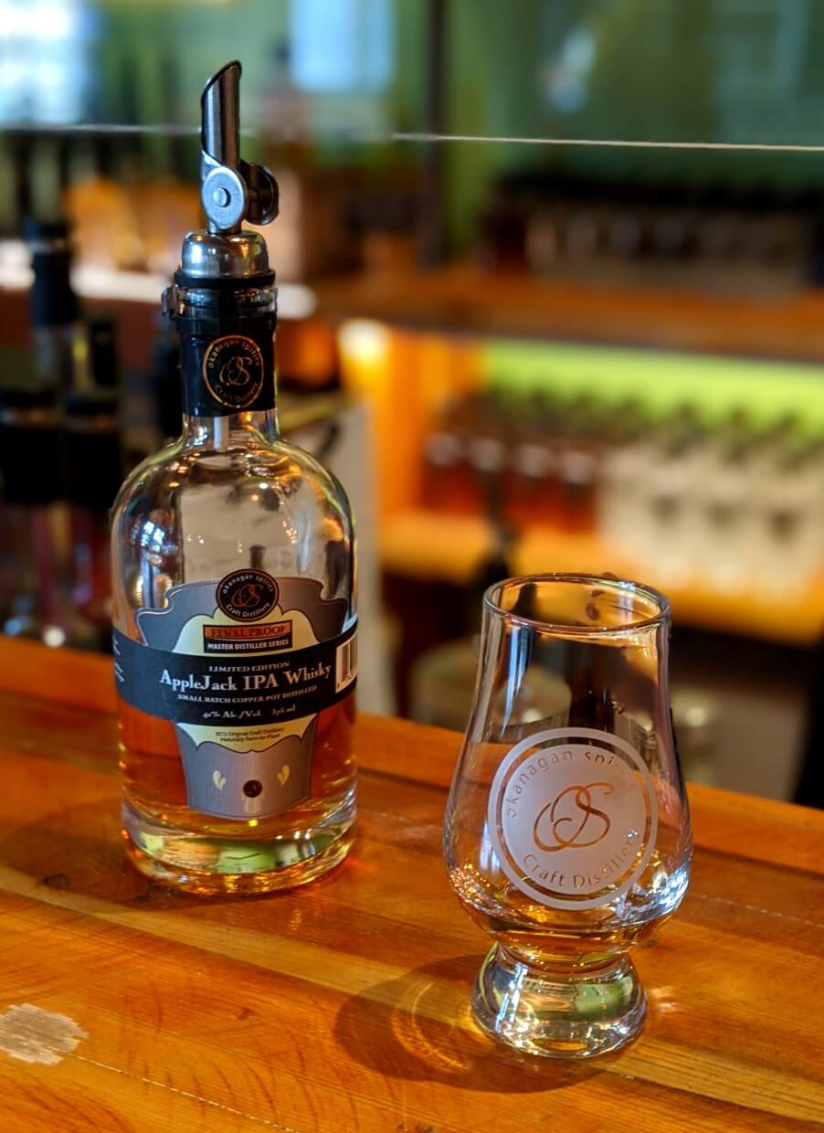 An Okanagan Spirits glass sits on a wooden countertop with a bottle of AppleJack IPA Whisky behind