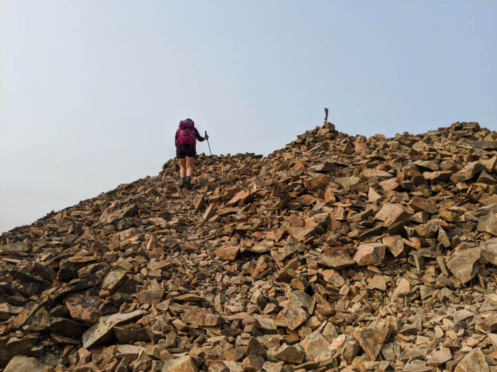 Gemma hiking through scree on Frosty Mountain ridge, almost at the summit