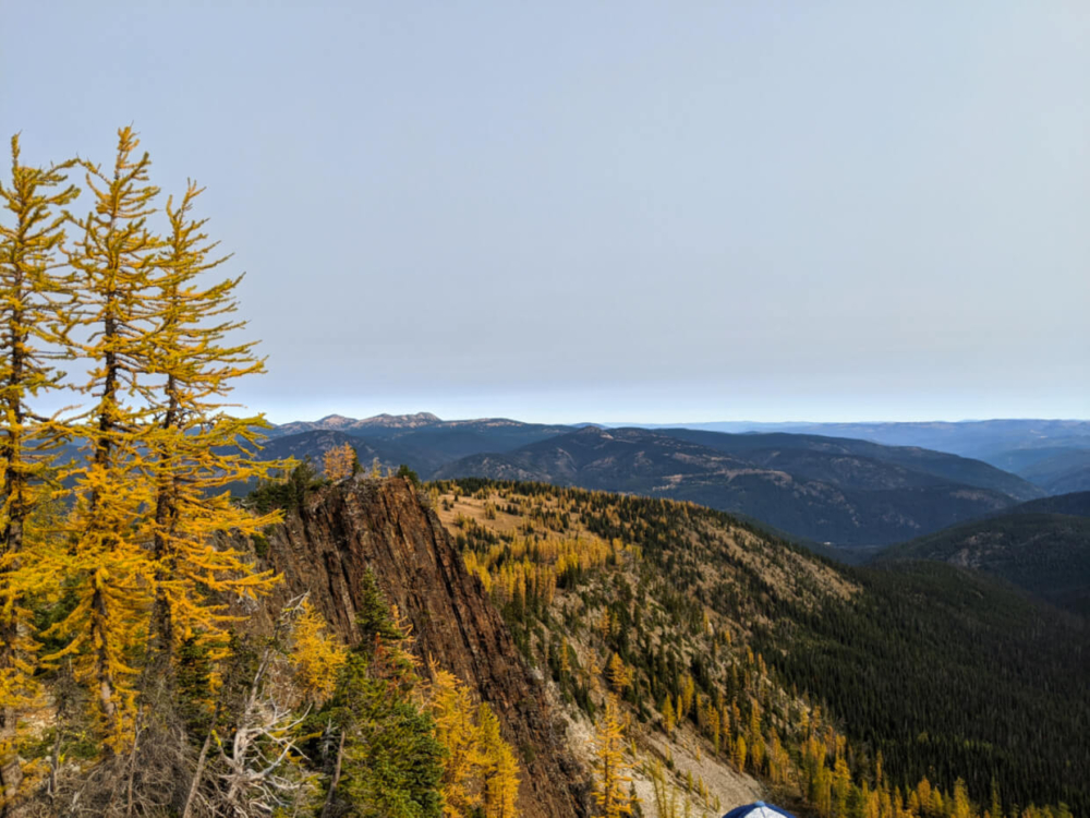 Looking down the Frosty Mountain Trail from high point with golden larch trees below and mountain views