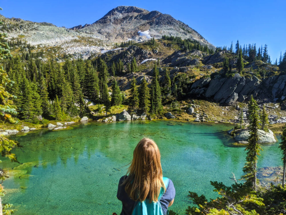 View of Gemma sitting in front of turquoise coloured lake, surrounded by subalpine terrain and mountain