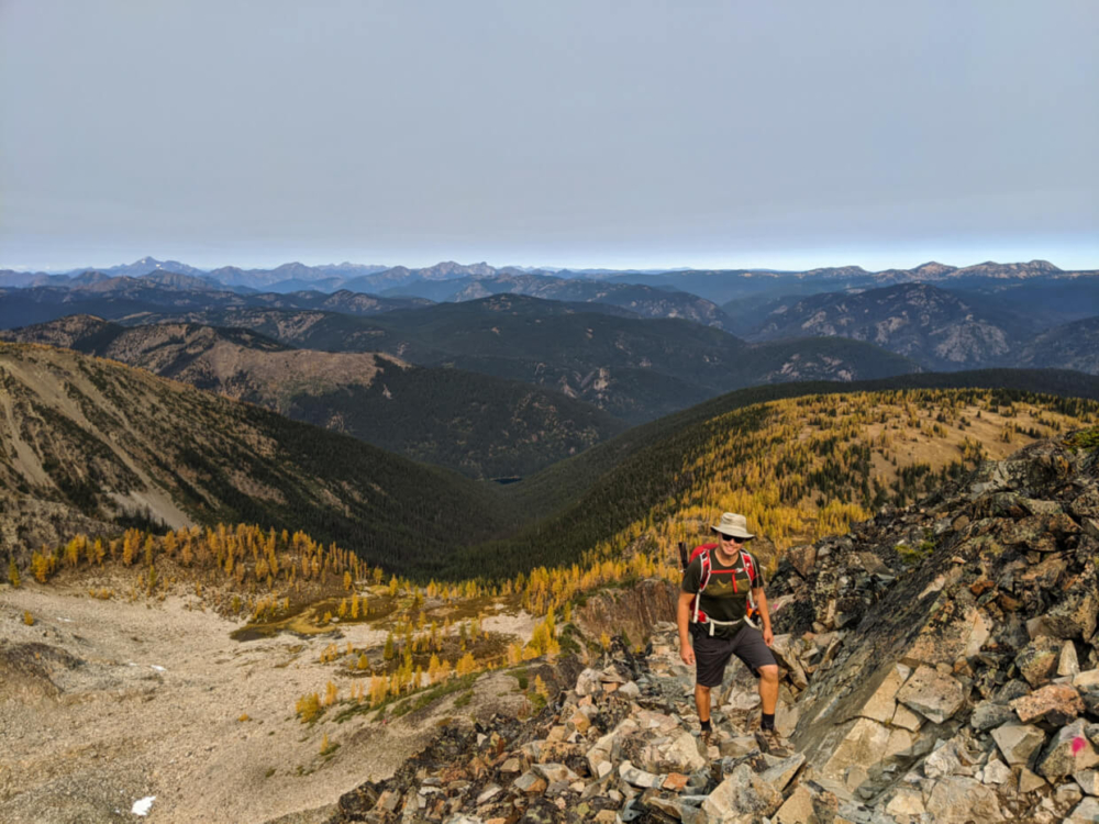 JR hiking up scree to ridge on Frosty Mountain Trail, with backdrop of mountains