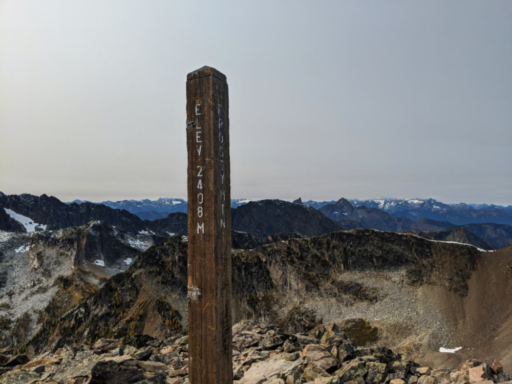 Frosty Mountain summit with wooden summit sign, stating elevation of 2408m, with mountain peaks in background