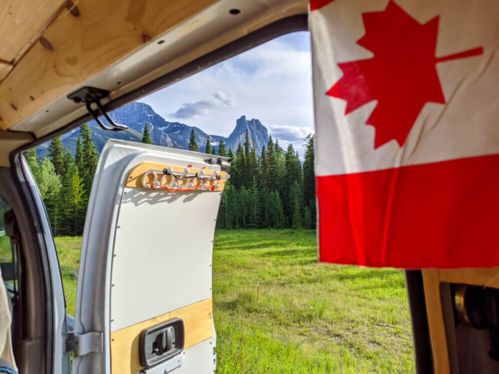 View out of side door of van conversion with mountains in background and Canadian flag in foreground