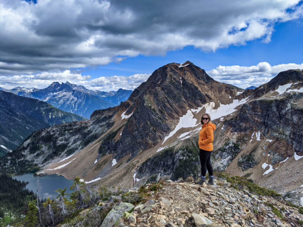 Gemma standing in front of lake and mountain view at Jade Pass, Mount Revelstoke National Park
