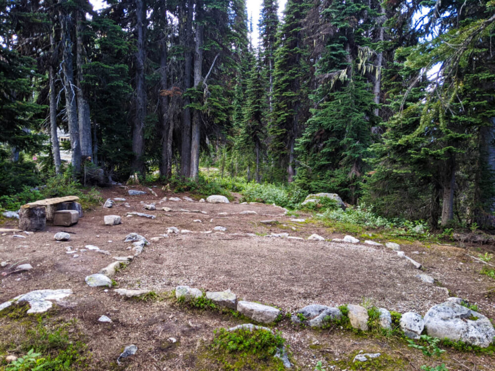 Two dirt tent pads bordered with rocks at Eva Lake campground