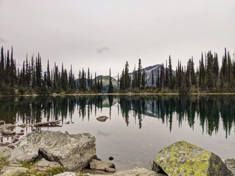 View of Eva Lake with calm reflective surface, cloudy sky