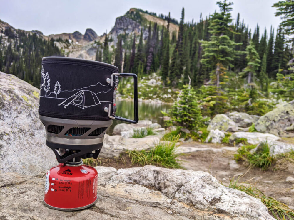 Black and white camping stove on top red gas cannister, placed on a rock in front of a mountainous view