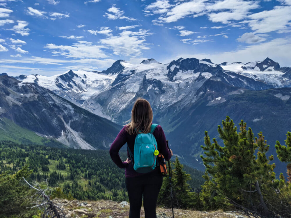 Back view of Gemma standing in front of magnificent view with mountains and glaciers, Jumbo Pass, BC
