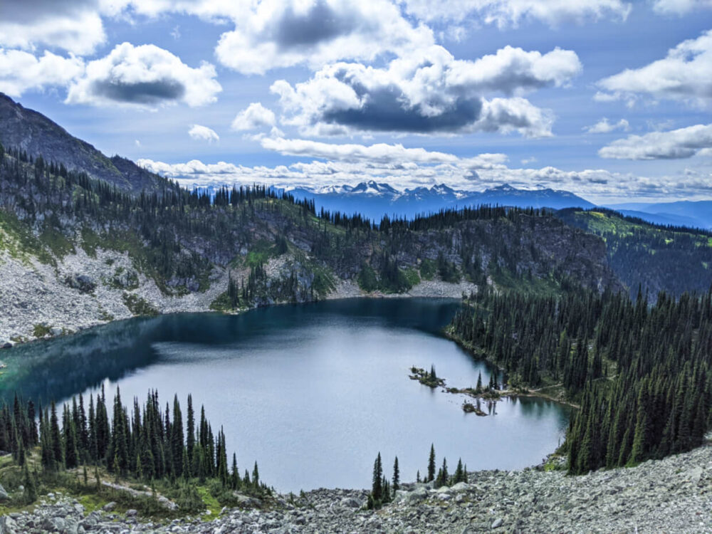 Looking down to a large deep blue lake from hiking trail, backdropped by mountains