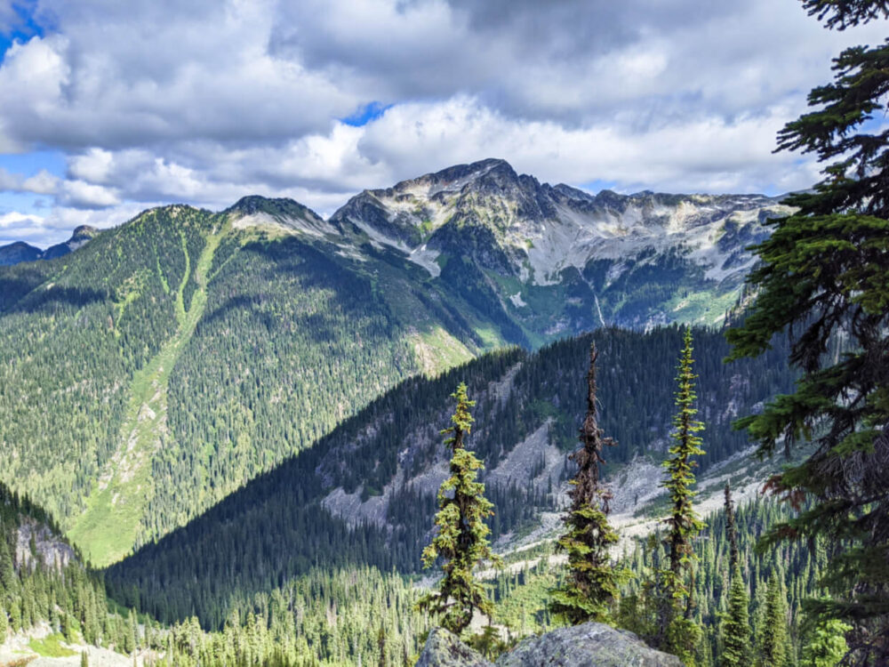 Forested mountain slopes and rugged peaks as seen from peek through viewpoint at Eva Lake