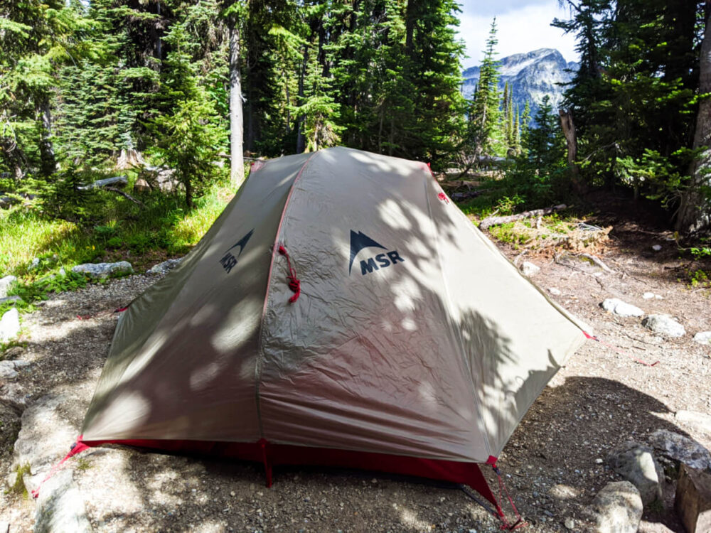 MSR tent set up on dirt tent pad near Eva Lake, with mountain peak in the background, seen through the trees