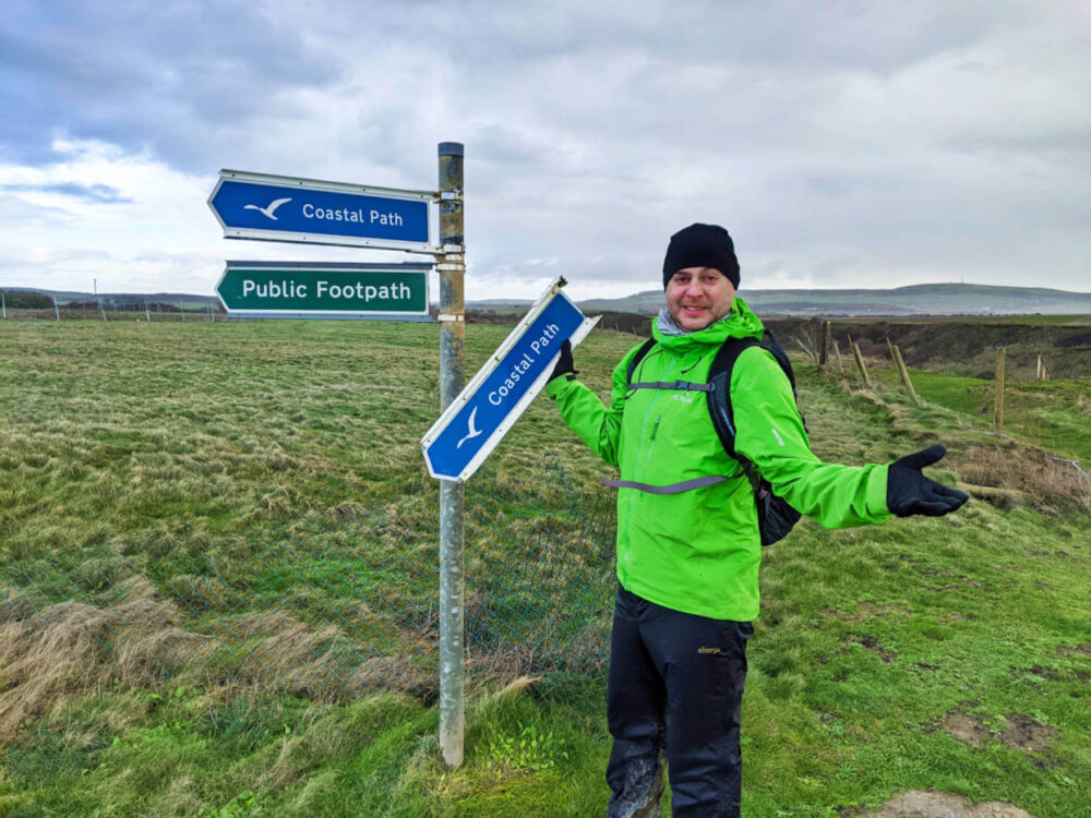 JR standing in front of Isle of Wight Coastal Path signs, holding one in hand that has fallen onto ground after storm