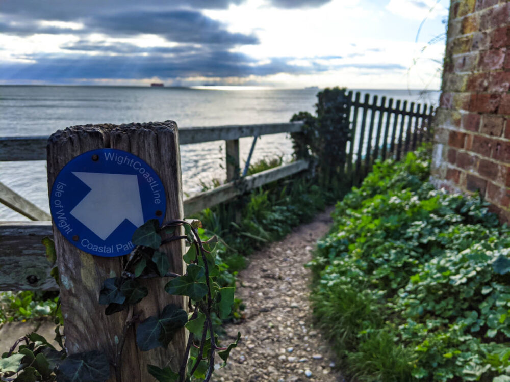Isle of Wight Coastal Path blue sign on wooden post next to trail with ocean in background