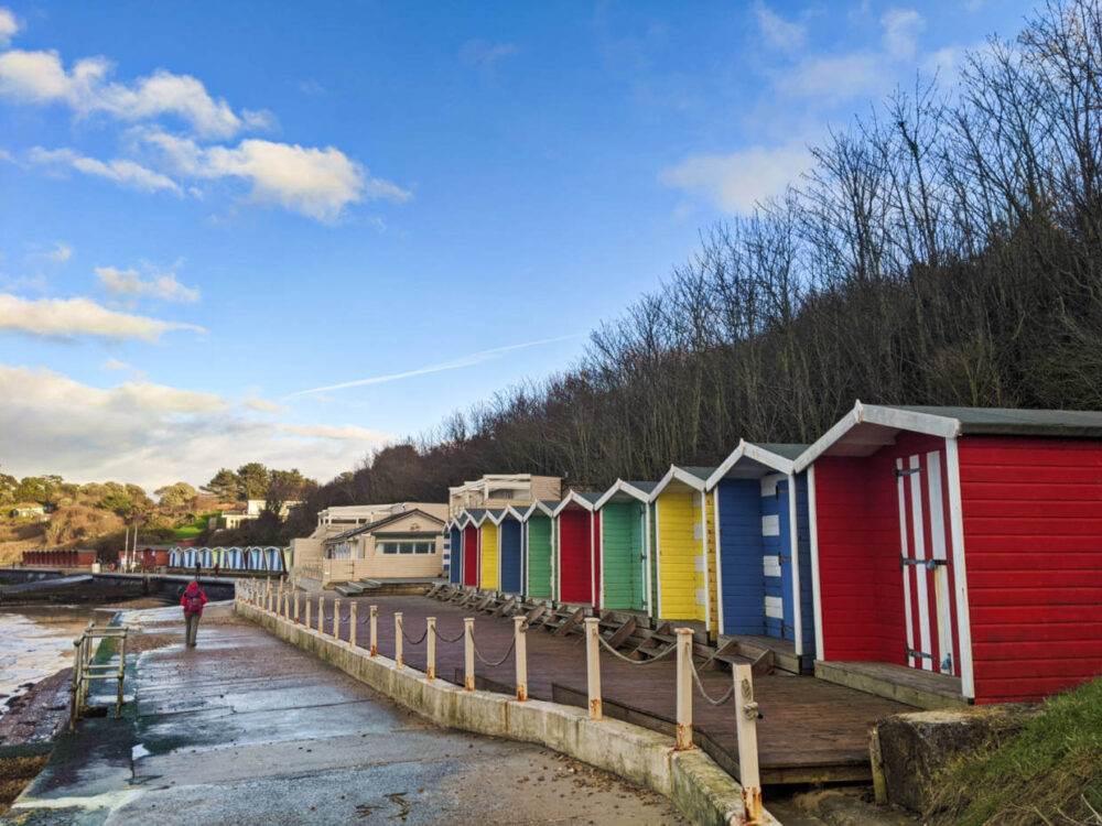 Brightly coloured beach huts next to paved promenade on the Isle of Wight Coastal Path