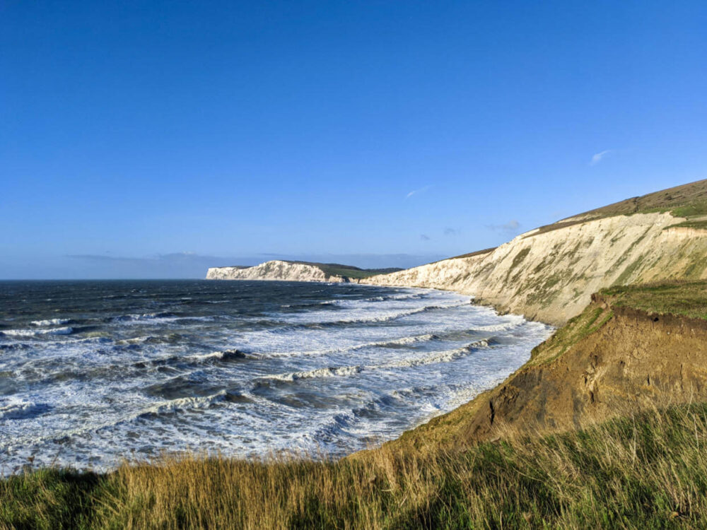 Looking out along the chalk cliffs from Compton Farm area, with ocean waves approaching