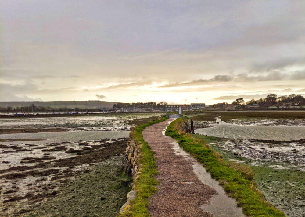 Looking ahead at gravel causeway path with low tide on either side, bright sky ahead