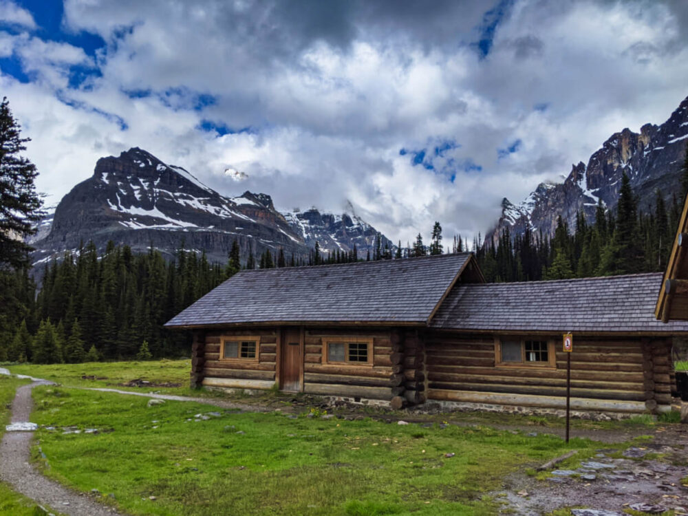 Long wooden cabin with grey roof in subalpine meadow, with backdrop of trees and mountains