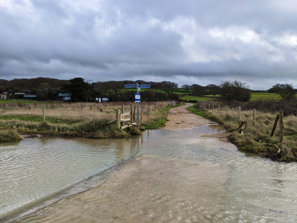 Flooded road with St Catherine's Lighthouse trail signs leading away from the water