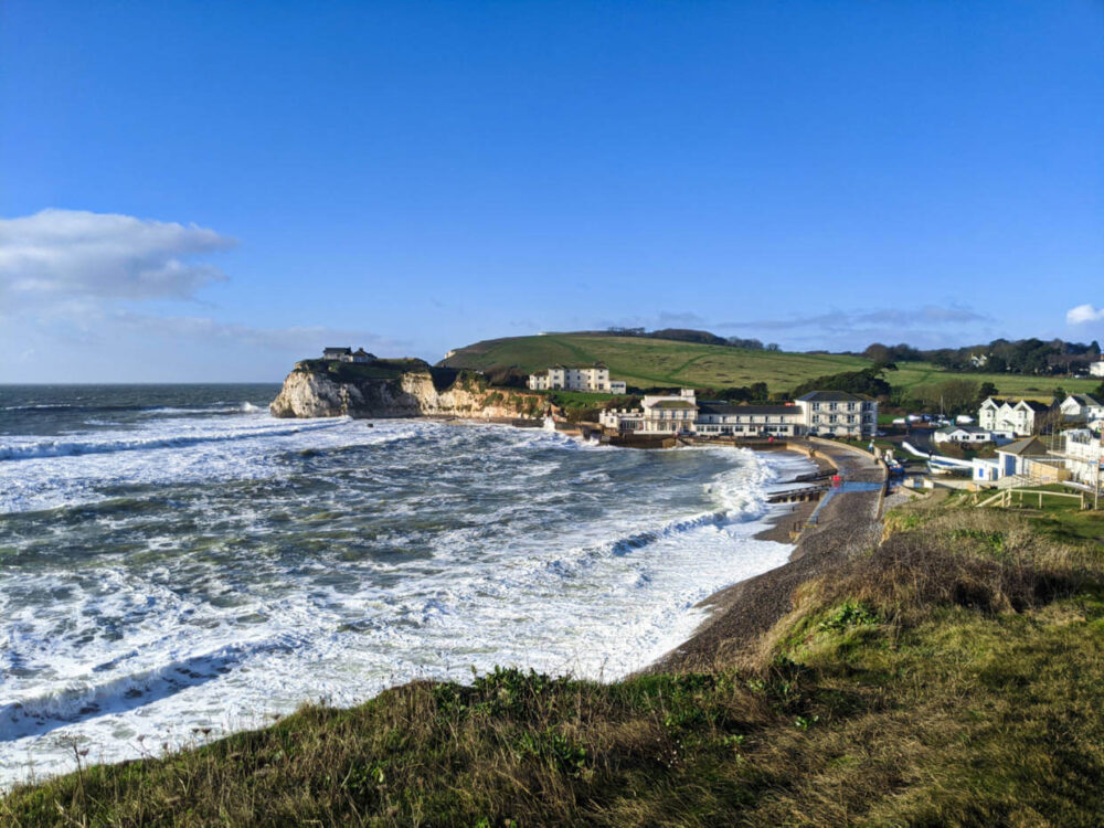 Following the Isle of Wight Coastal Path to reach the small community of Freshwater Bay, with large ocean waves rolling onto the shingle beach