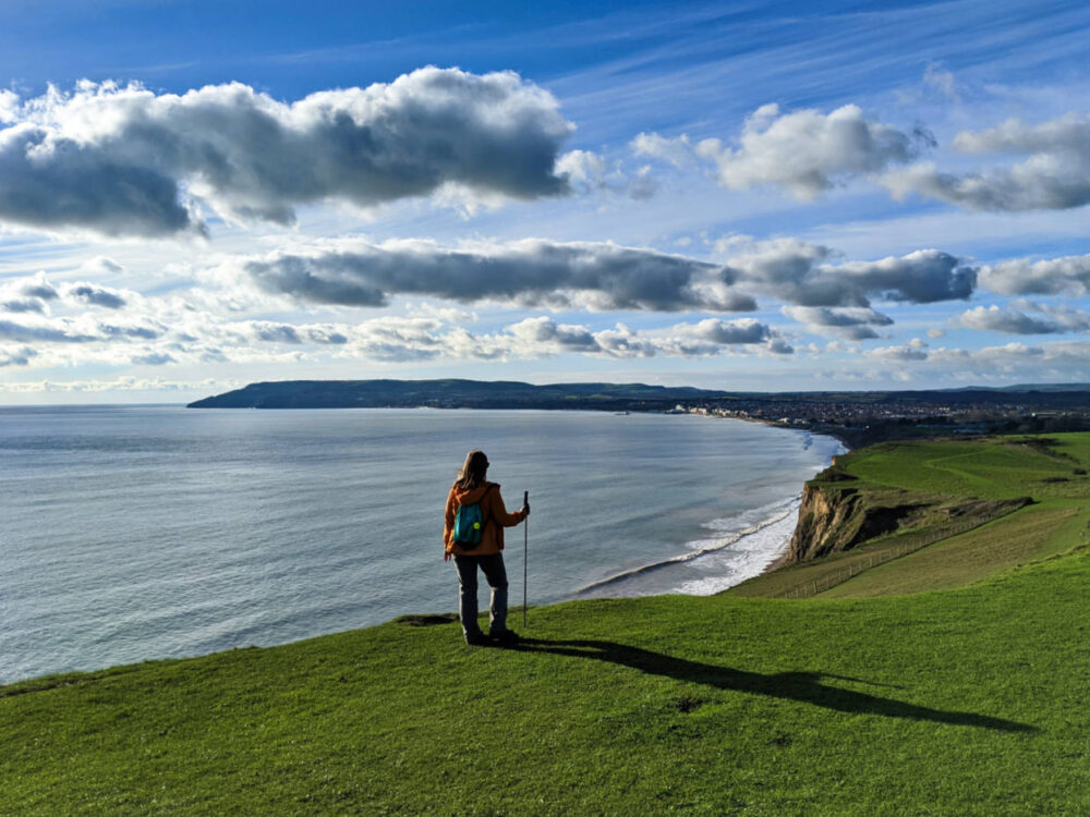 Gemma standing with hiking pole and back to camera at the top of grassy Culver Down, with views down the coast of Sandown an Shanklin