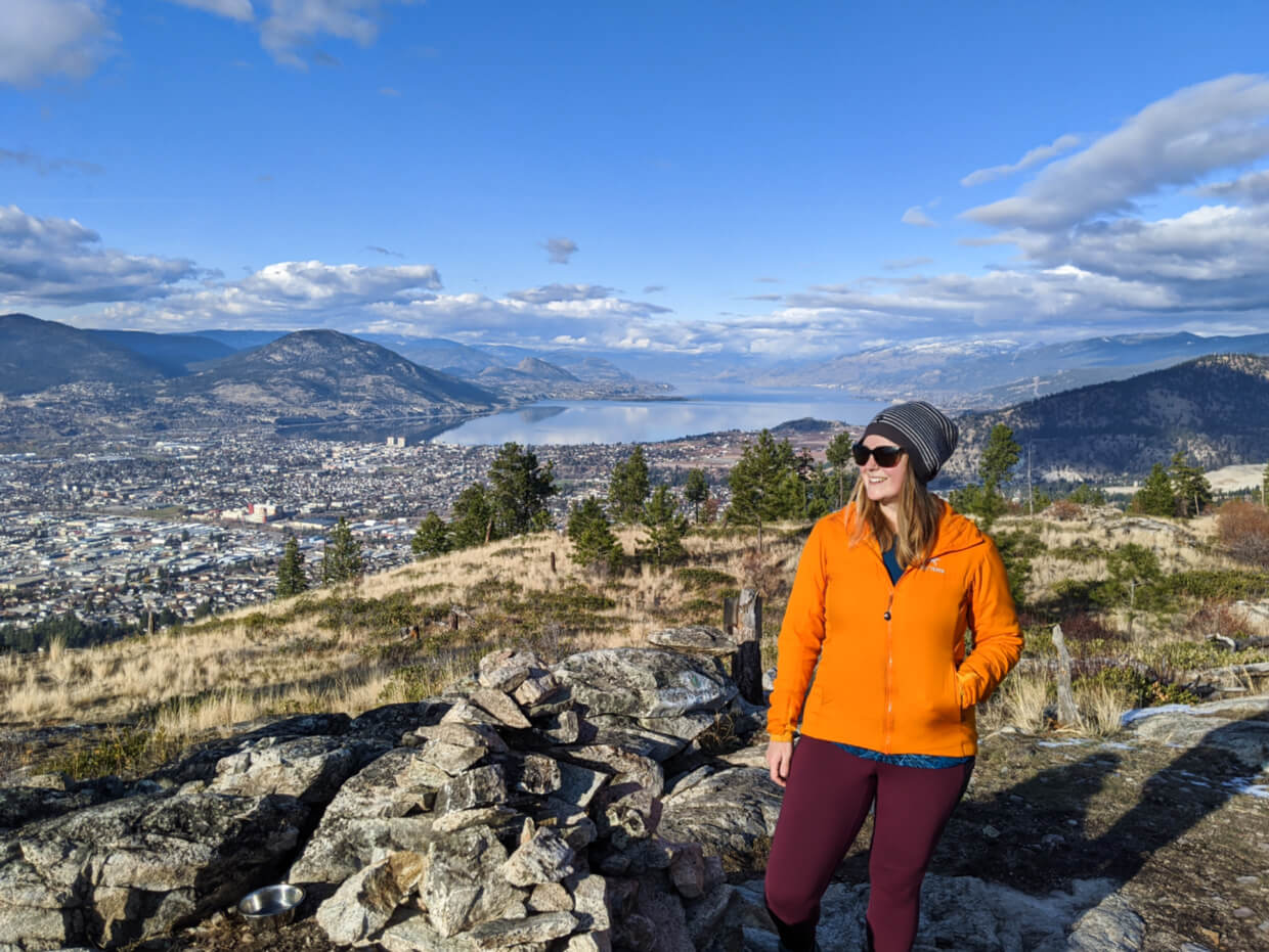 Gemma standing by pile of rocks at top of mountain summit with view of Penticton city centre behind with lake and surrounding mountains