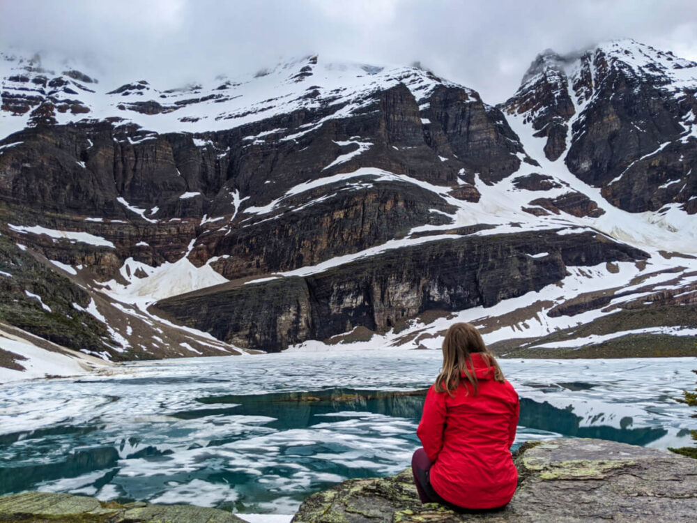 Gemma sits in front of partially frozen Lake Oesa, with turquoise water visible below the ice. The lake is surrounded by snowy mountains