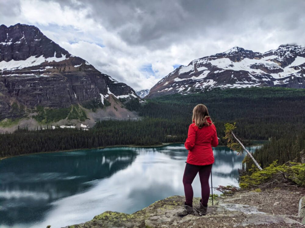 Gemma standing in front of elevated view of Lake O'Hara below, backdropped by snow topped mountains