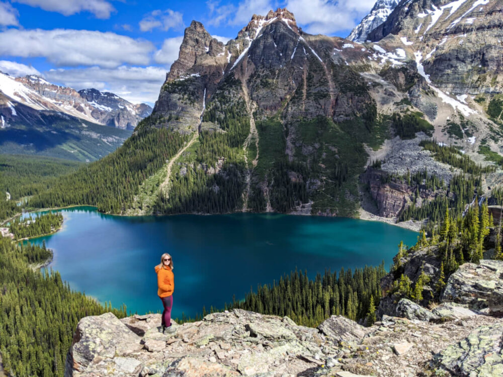 Gemma standing on rocky ledge in front of beautiful mountain scenery including deep blue lake lined by mountains