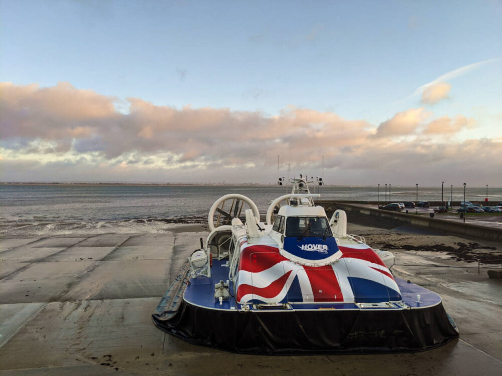 Hovercraft on cement beach in Ryde with Union Jack decoration and sunrise colours in background