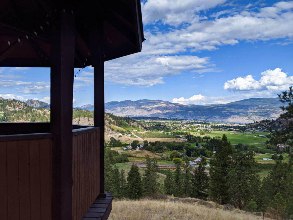 Side of wooden gazebo with views of the orchards and vineyards of Summerland below, with rolling mountains in the background