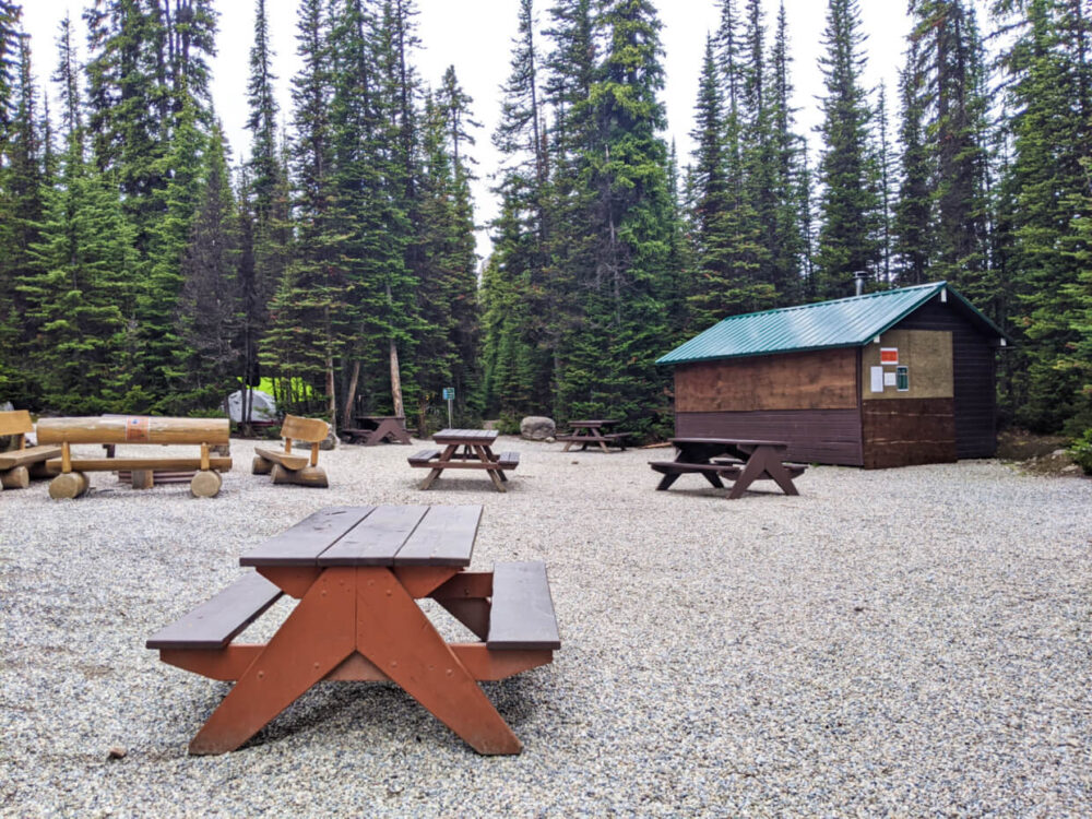 Communal area at Lake O'Hara campground with spaced picnic tables, shelter (closed up due to Covid precautions) and a fire pit, with tents seen through the trees in the backcountry