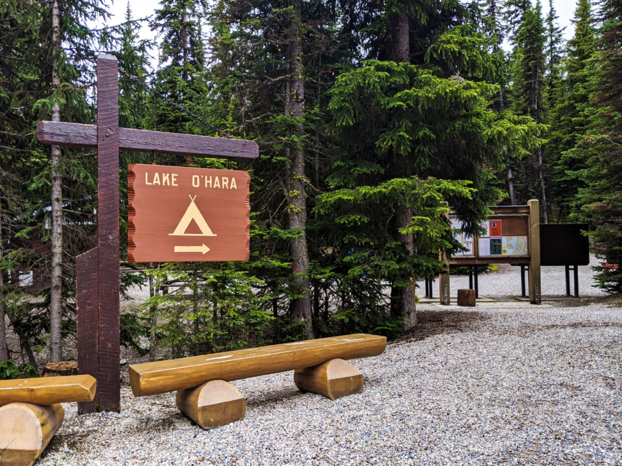 Wooden Lake O'Hara campground sign with benches signifying bus stop with campground entrance behind