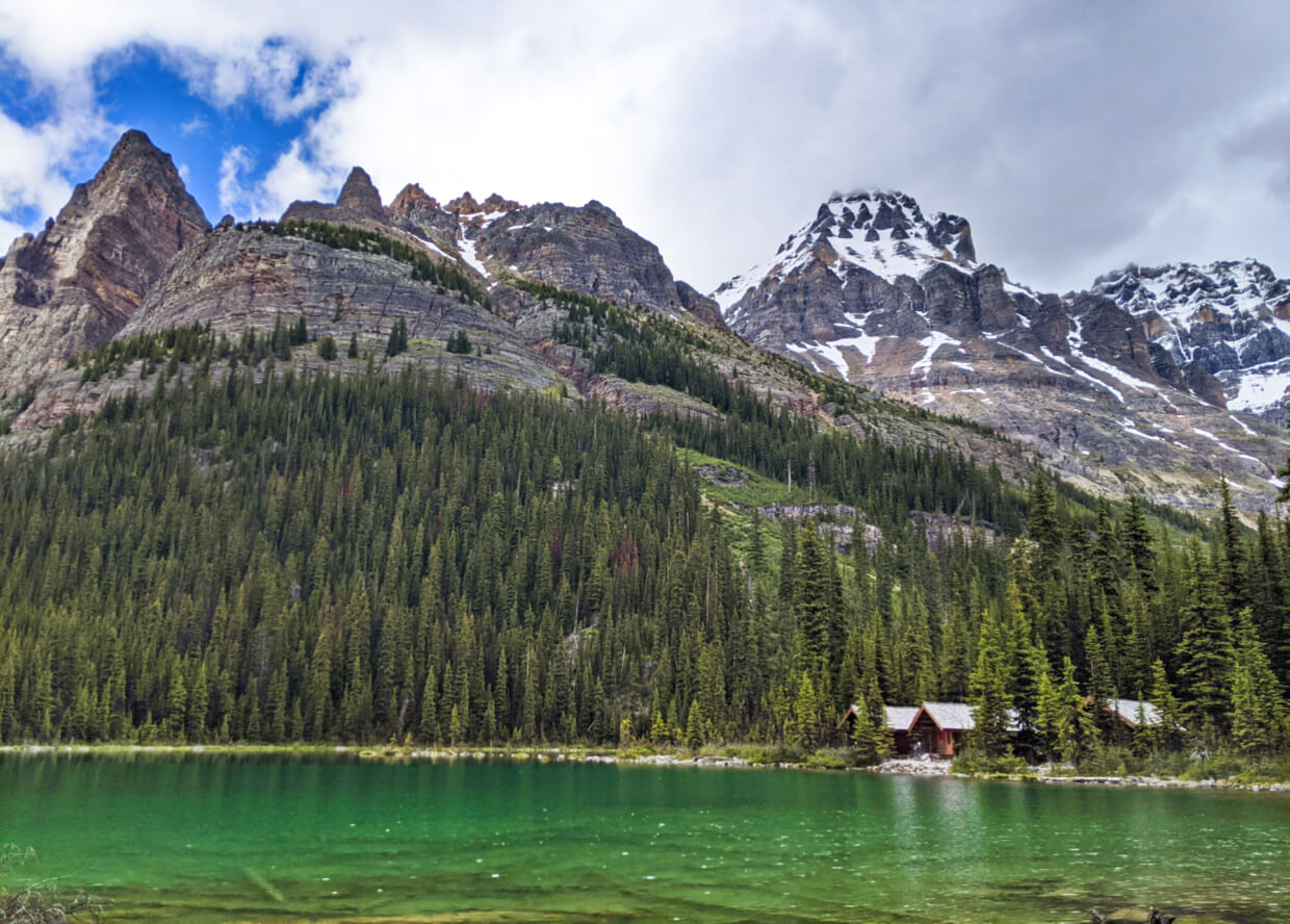 Lakeshore views of Lake O'Hara with mountains rising above cabins and emerald coloured water