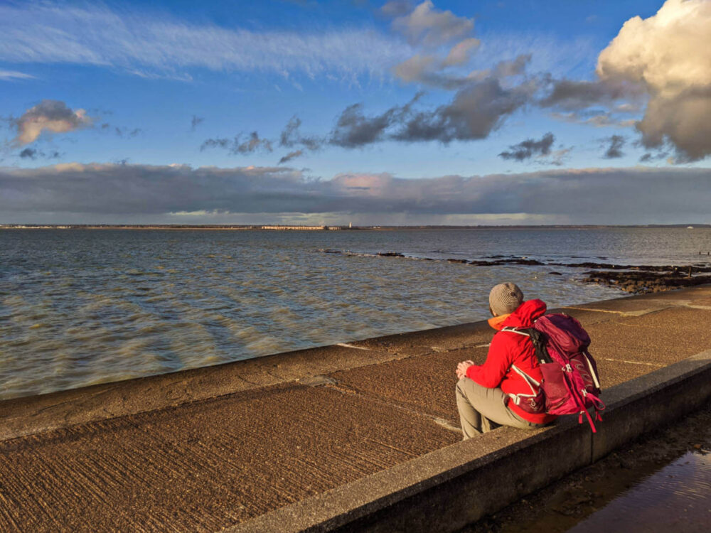 Gemma sat on concrete wall next to Isle of Wight Coastal Path, looking out to calm ocean with Hurst Castle in background