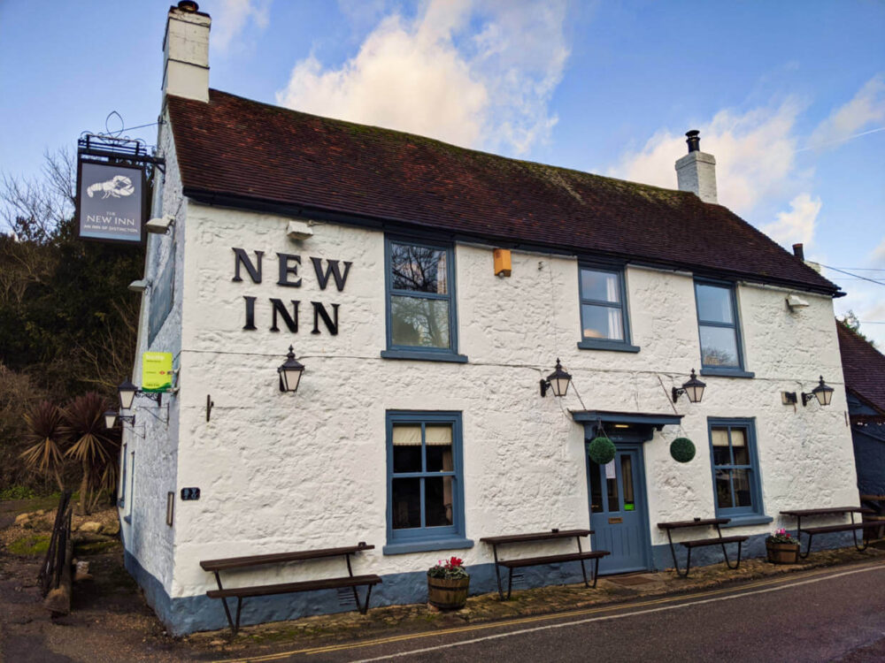 White pub building with New Inn name on side