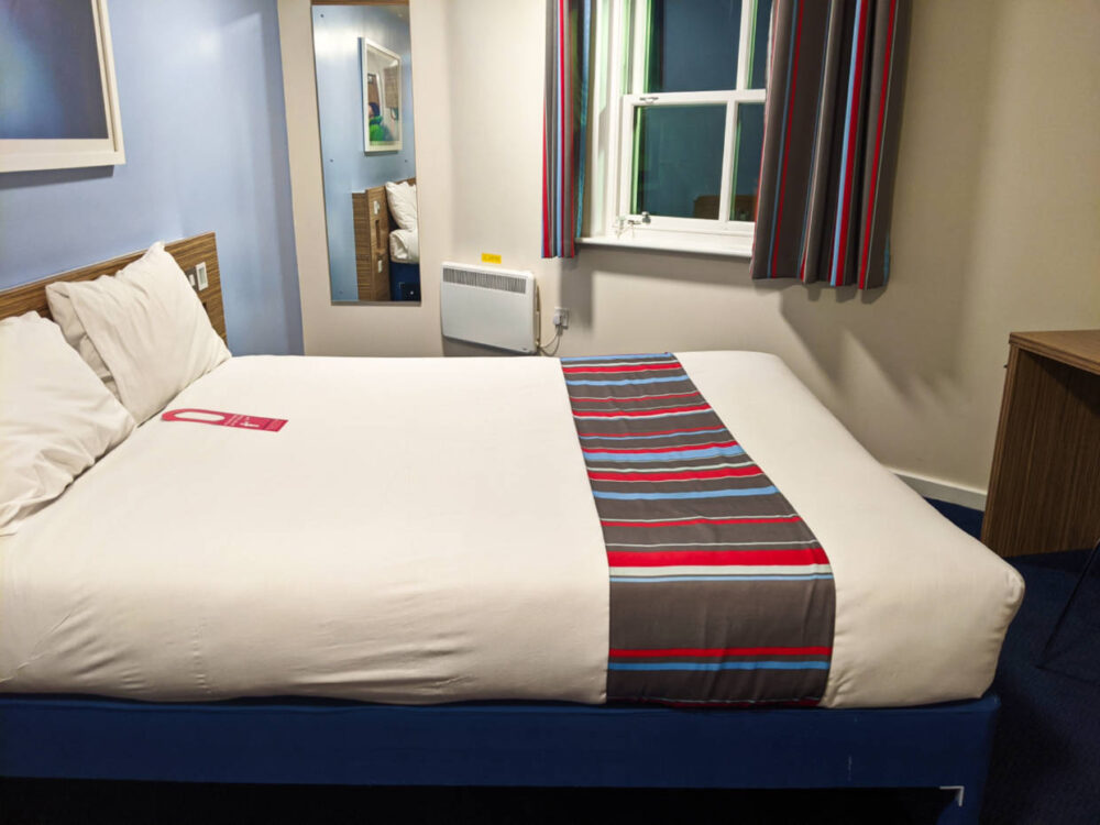 Hotel room at Newport Travelodge with made bed, desk in front of bed, window and mirror behind bed