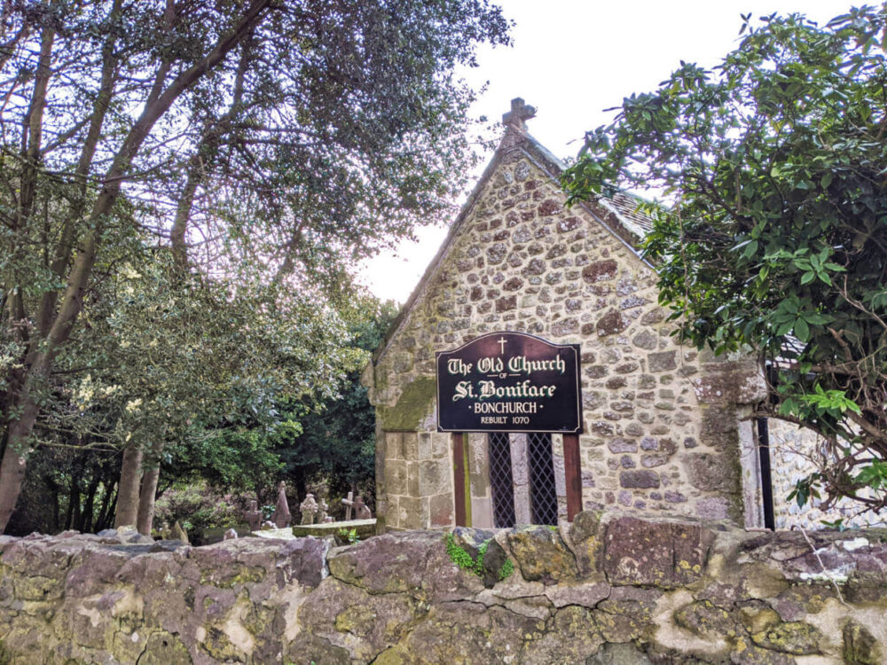 Looking over stone wall to one story 11th century Old Church of St Boniface on Isle of Wight