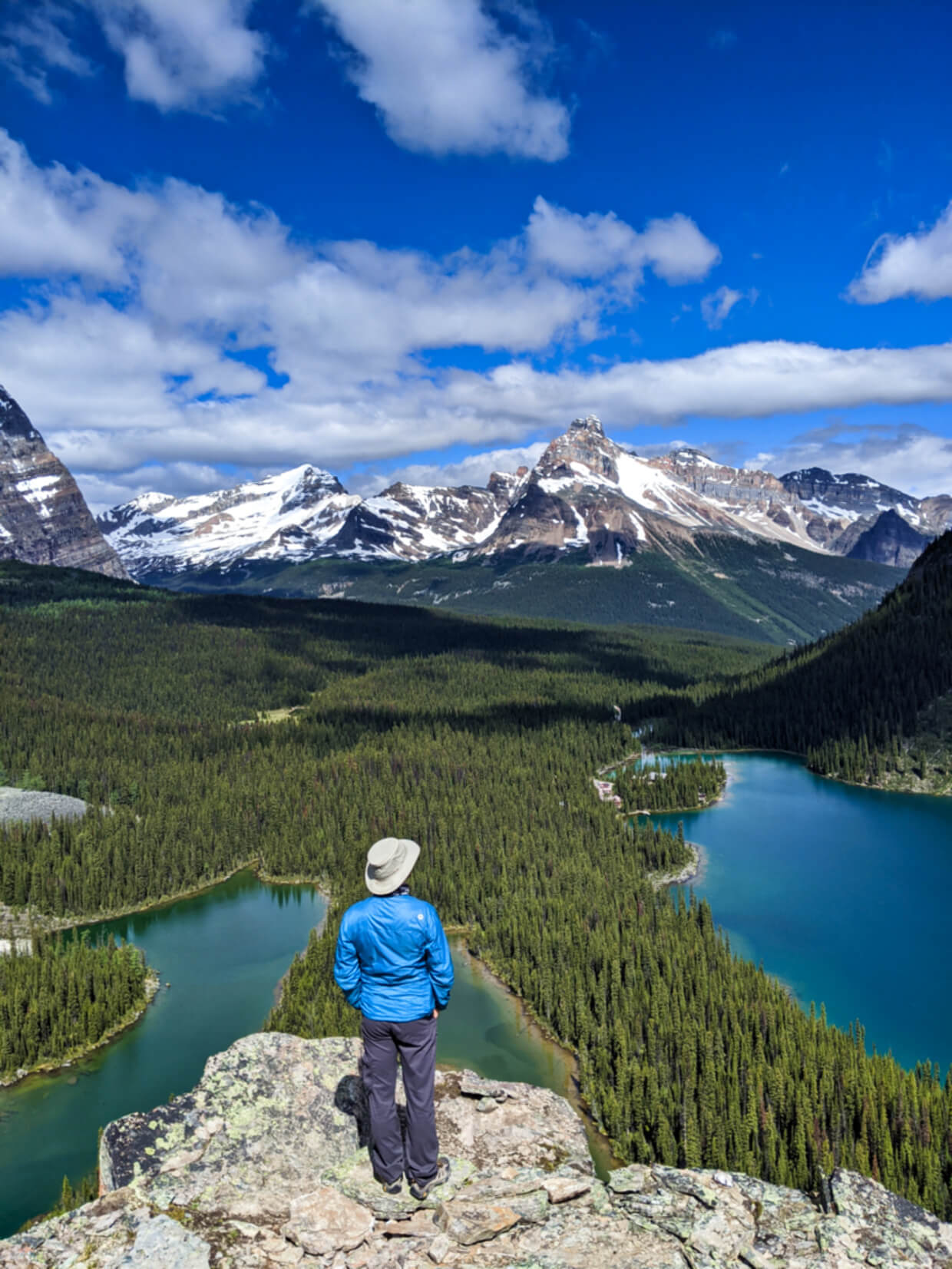 JR standing on rocky elevated viewpoint looking down on three lakes, backdropped by mountains