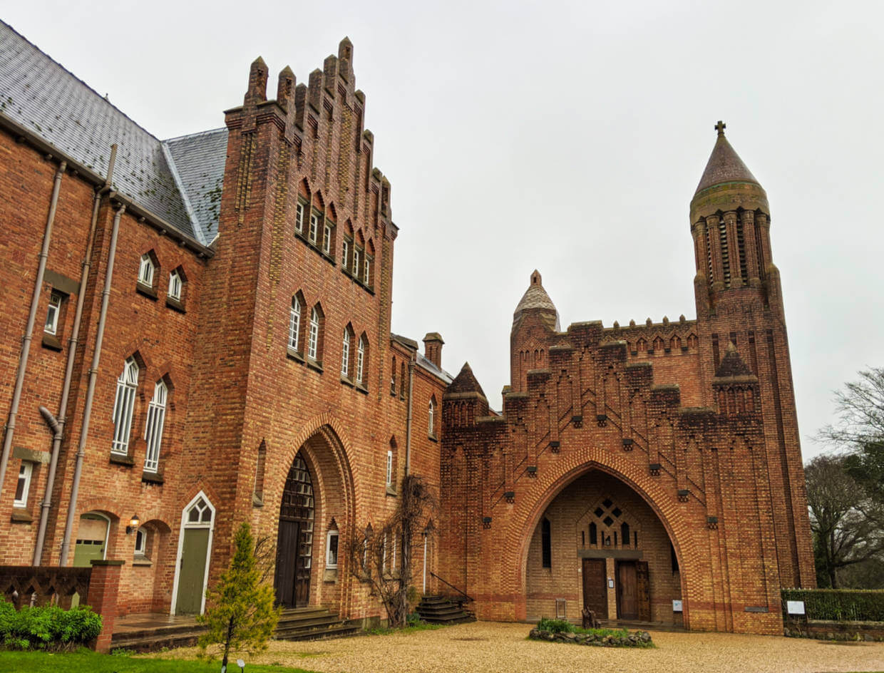 Orange coloured brick monastery building, part of Quarr Abbey