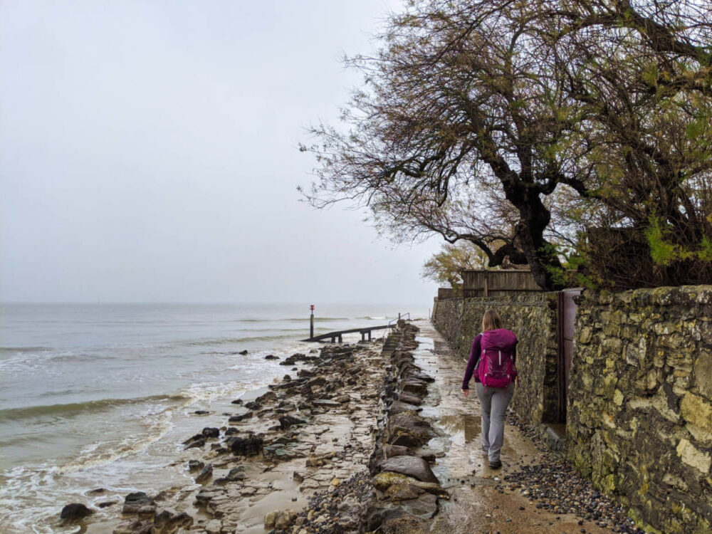 Gemma walking along narrow paved trail next to ocean on Isle of Wight Coastal Path