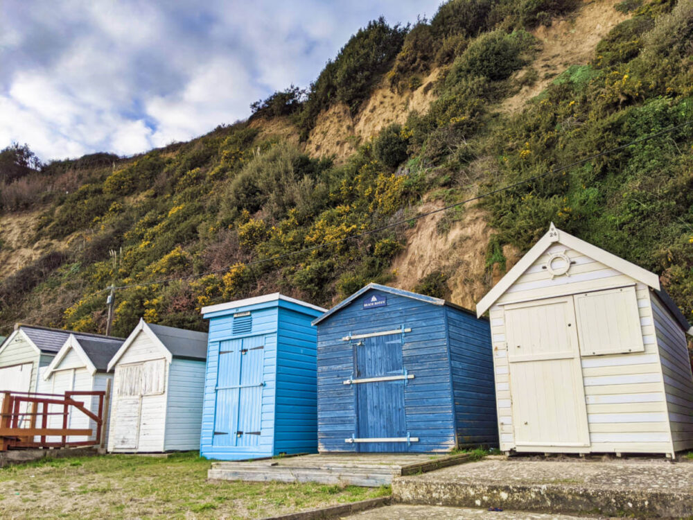 Six beach houses, two of them blue, next to cliff covered in foliage backing onto Shanklin beach on the Isle of Wight