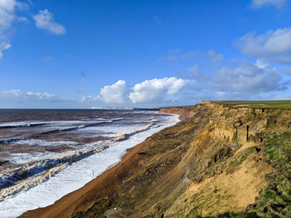 Looking across cliffs on south coast of Isle of Wight, with ocean wavs rolling in and chalk cliffs in distance