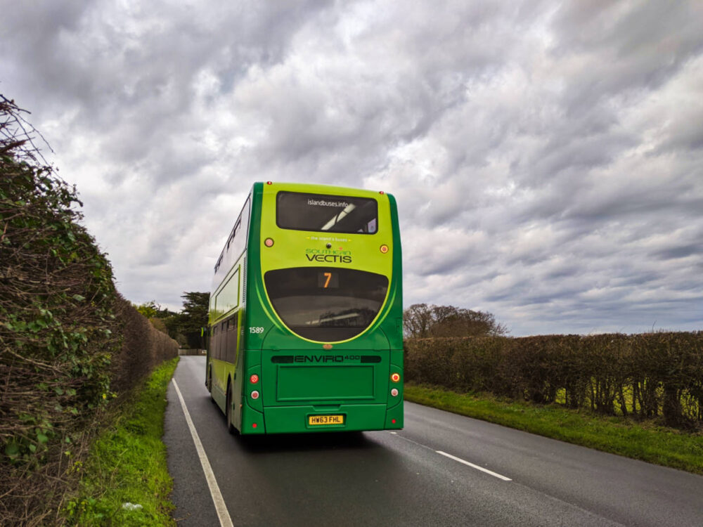 Green double deck Southern Vectis bus driving away on road