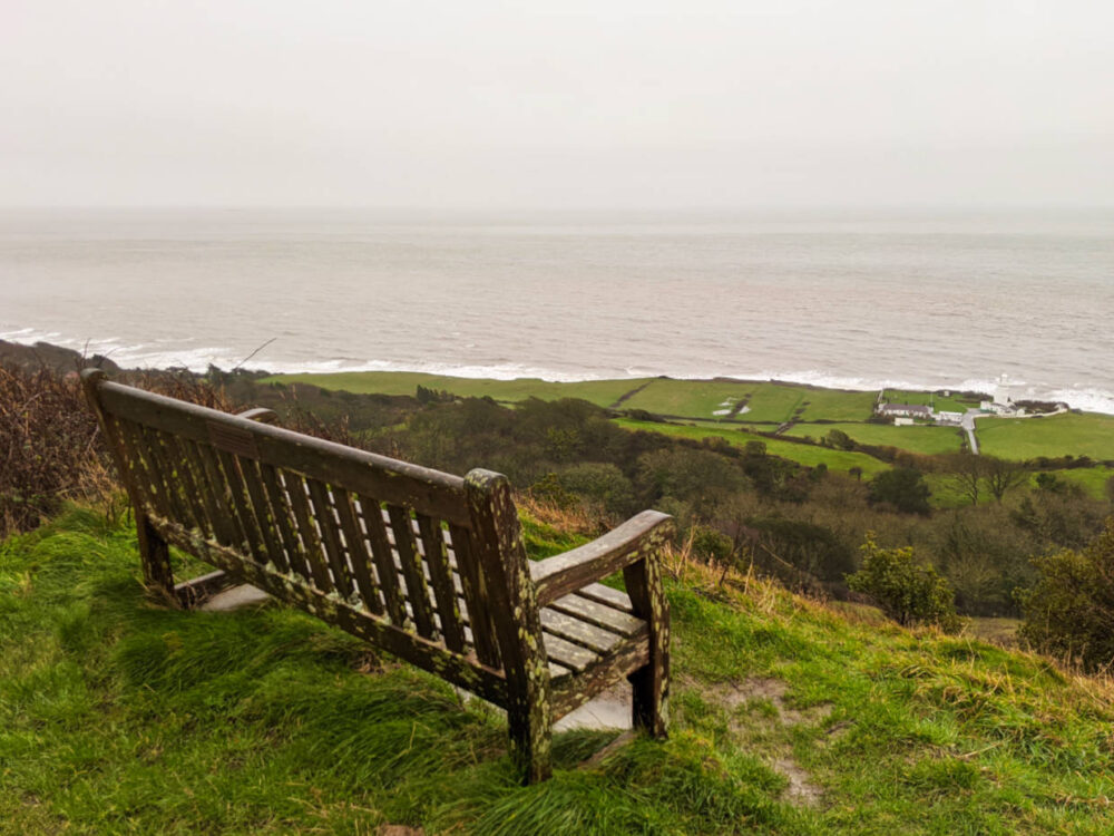 Elevated view past bench looking down on grass fields and lighthouse in front of grey ocean on the Isle of Wight Coastal Path