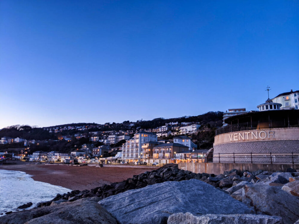View looking back at town of Ventnor next to English Channel with shingle beach and bandstand with 'Ventnor' on it