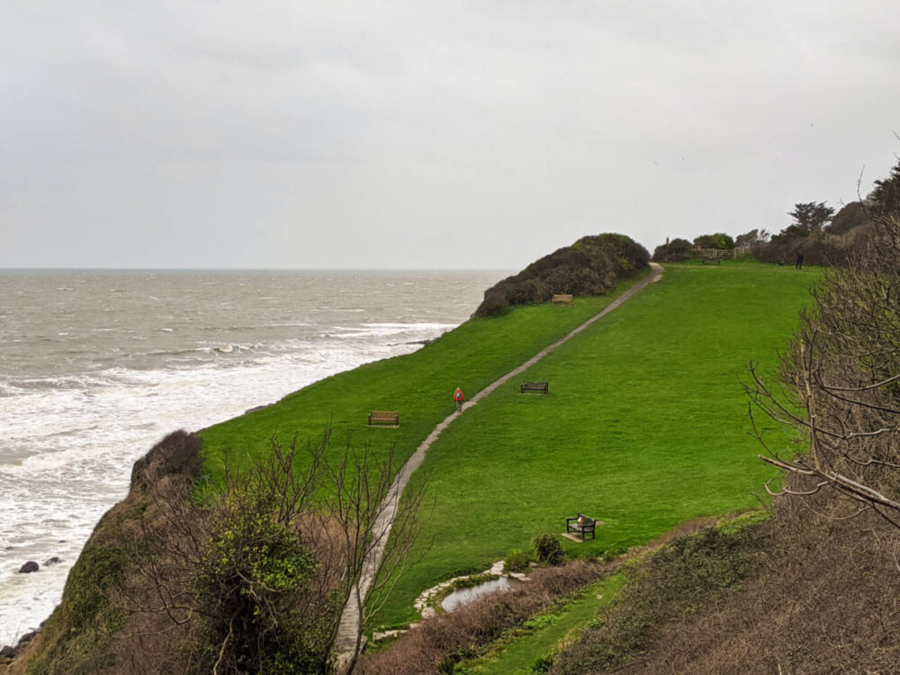 Gemma walking along paved path at side of cliff, with ocean raging in background