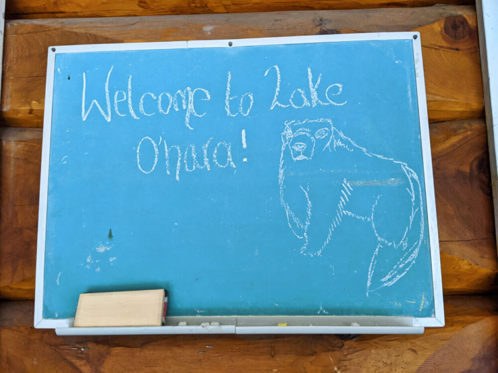 Chalkboard on cabin wall with 'Welcome to Lake O'Hara' and a drawing of a marmot in chalk
