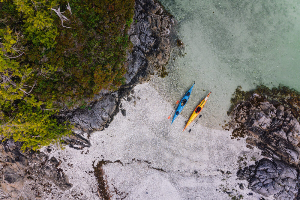 Top down view of kayaks on shore, landing on one of the islands in the Broken Group. Light coloured rock beach with clear ocean water, overhanging trees